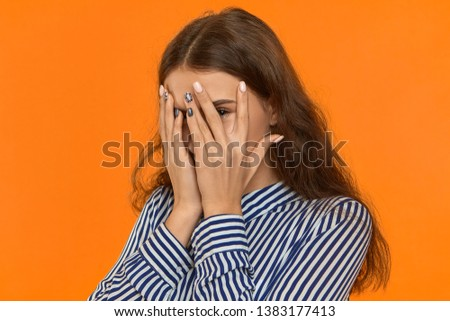Scared young Caucasian female hiding her fear behind hands. Portrait of shy, timid or ashamed pretty girl covering face and peeping through fingers, looking at camera, being curious. Body language stock photo