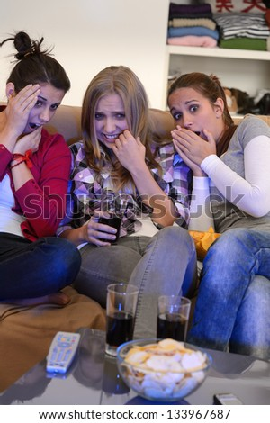 Scared young girls watching horror movie on television
