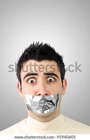Scared young man having gray duct tape on his mouth.Gradient background with copy space.