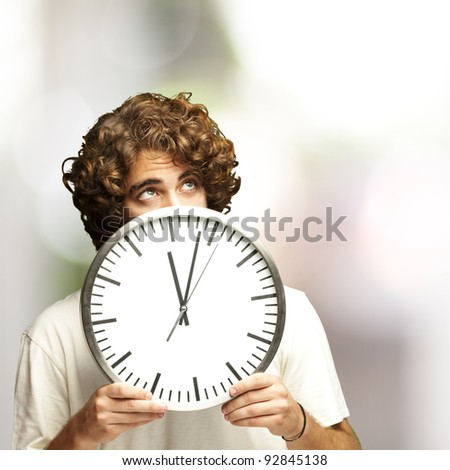 scared young man hidden behind a clock against a abstract background