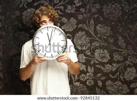 scared young man hidden behind a clock against a vintage wall