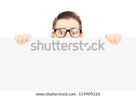 Scared young man with glasses hiding behind a blank panel isolated on white background