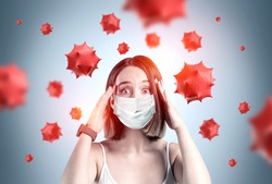 Scared young woman in medical mask standing over gray background with blurry red virus molecules. Concept of coronavirus and flu panic. Toned image