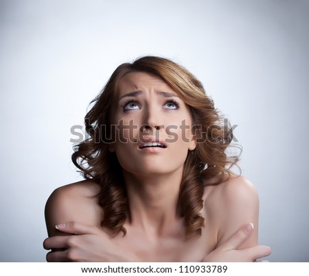 Scared young woman looking up