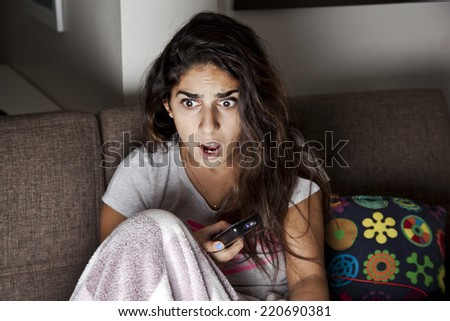 Scared young woman watching tv. Brunette girl sitting on couch with remote control