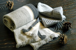 Scarf and knitted hat in gray, pine cones close-up on a dark wooden surface.