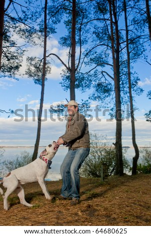 scary and strong big white bulldog having practice time with its master trying to pull him  by rope using mouth and sharp teeth. shoot with studio strobe