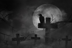 Scary background the black crow perched on cemetery cross in fog dark and light with dark silhouette in large moon and abandoned large cities, concept of horror and Halloween