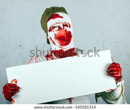 scary bloody zombie blind in cap holds a sheet of light plastic.invitation to halloween