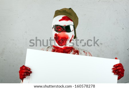 scary bloody zombie wearing a cap and glasses holding a sheet of light plastic.invitation to halloween