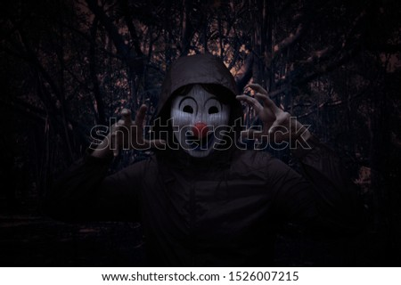 Scary evil clown wear jacket standing over spooky dark forest with tree, leaves and vine, Halloween mystery concept