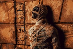 Scary evil mummy stands by an ancient Egyptian tomb. Halloween. Ancient Egyptian mythology.