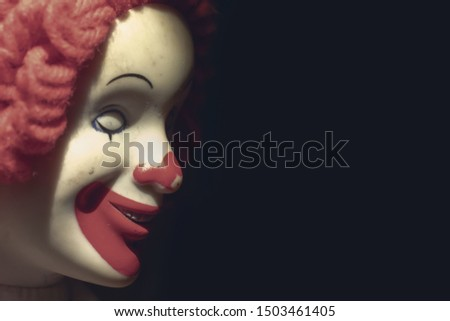 Scary evil sinister clown face with a spooky smile on black background with copy space, coulrophobia and fears concept. #1503461405