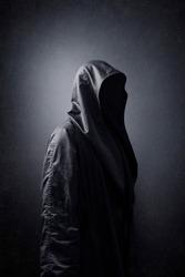 Scary figure in hooded cloak in the dark.