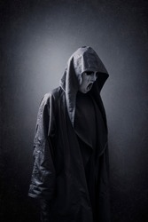 Scary figure with mask in hooded cloak in the dark