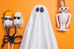 Scary ghost phantom dresses up for halloween poses against orange background with spooky creatures around enjoys mystery holiday celebration on 31st of October has scary look supernatural power