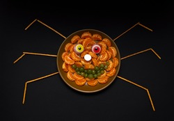 Scary halloween food spider face for celebration party decoration. Children's holiday food made from fruits, sweets