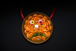 Scary halloween food vampire or demon monster face for celebration party decoration. Children's holiday food made from fruits, sweets