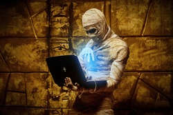 Scary Halloween mummy holds a laptop standing by the wall with ancient Egyptian hieroglyphs. Halloween. Ancient Egyptian mythology.