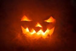 Scary Halloween Pumpkin looking through the smoke. Glowing, smoking monster pumpkin from depths of hell