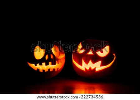 Scary Halloween pumpkins isolated on a black background. Scary glowing faces trick or treat