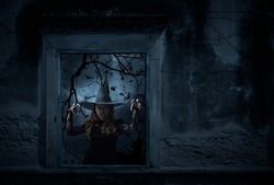 Scary halloween witch standing in old damaged window with wall over cross, church, birds, dead tree and spooky cloudy sky, Halloween mystery concept