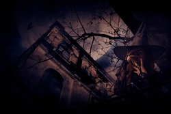 Scary halloween witch standing over grunge castle, dead tree, bird fly, full moon and cloudy spooky sky, Halloween mystery concept