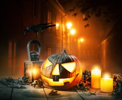 Scary horror background with halloween pumpkin jack o lantern, placed on wooden deck. Old town street on background with glowing lamps. Halloween spooky background.
