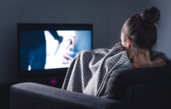 Scary horror movie on tv. Scared woman watching stream service hiding under blanket on couch at night. Sleepless person streaming series or film on television. Alone in dark and afraid of thriller.