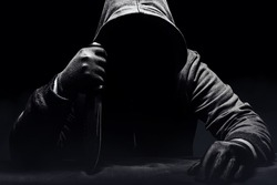 Scary horror photo of a man  in black hoodie sitting with knife.