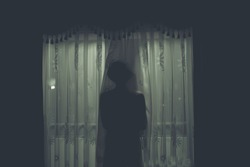 Scary human body silhouette woman front of window behind the black curtain.