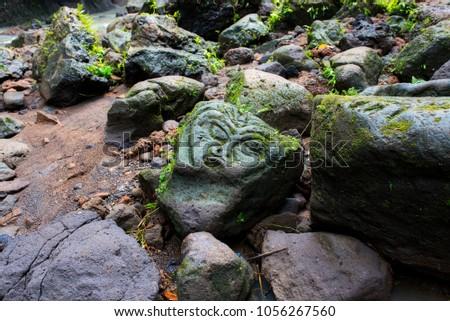 Shutterstock Scary idol carved on the stone near Tibumana waterfall in the jungles of Bali island, Indonesia