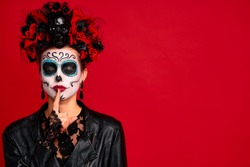 Scary lady calavera. wears artistic make-up for the feast of all the dead. Makes silence gesture keeps finger over lips, wears black leather jacket and lace gloves,dressed as skeleton isolated in red