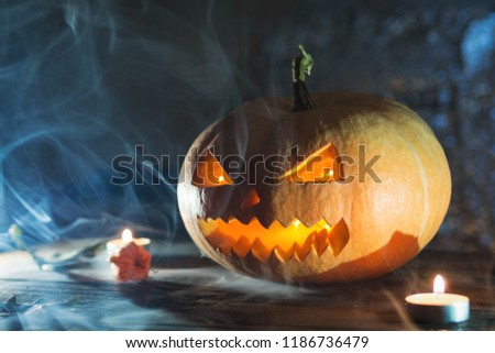 Scary laughing pumpkin lantern on dark background with copy space