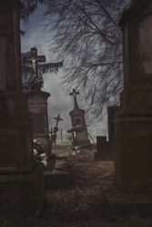 Scary leaning cross tomb stones in a foggy dark winter scene. Old creepy Christian graves on cemetery in Europe. Halloween wallpaper. Rest in peace. Spooky aged tombstones at grave yard with trees
