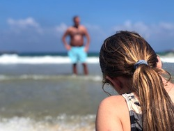 Scary Man watching a young girl on the beach. Child sitting alone on the beach of Tel Aviv, Israel. Over the shoulder of a young lady sitting on the shore with a harassing dark Man in the background.