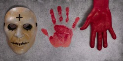 scary mask of a nurse and imprint of a bloody palm on cement