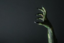 Scary monster on black background, closeup of hand with space for text. Halloween character
