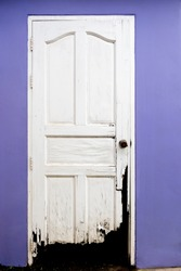 Scary old broken wooden white door and purple color wall. Concept for dirty, destroyed, abandoned.
