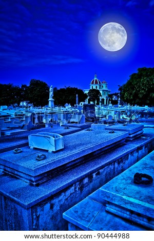 Scary old cemetery at night with a bright full moon shining over the graves - stock photo