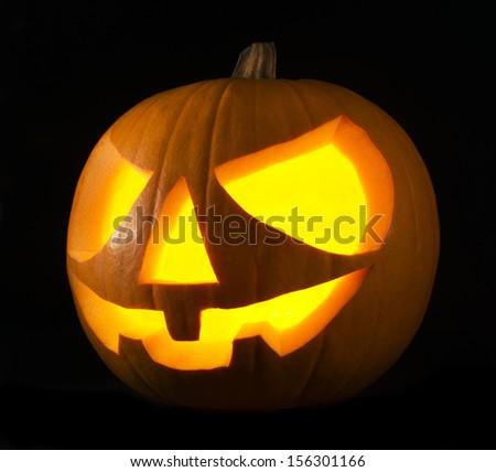 Scary old jack-o-lantern on black background close up - stock photo