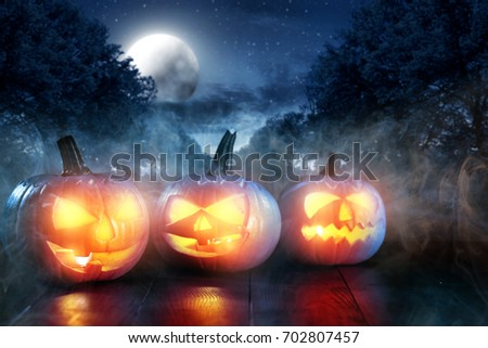 Scary pumpkin in a dark smoky garden on Halloween night #702807457