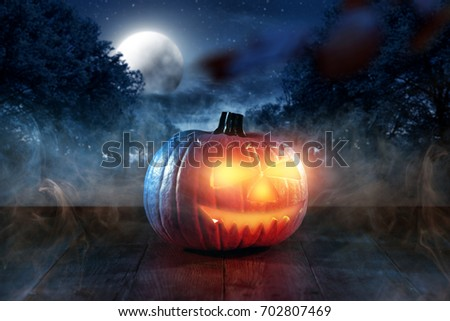 Scary pumpkin in a dark smoky garden on Halloween night #702807469