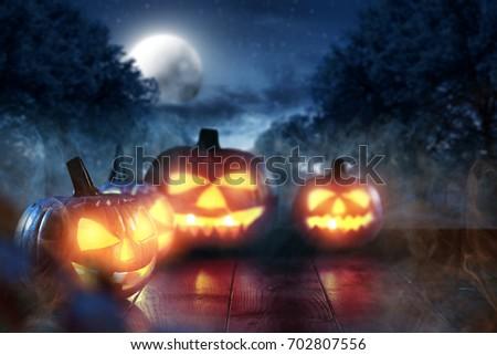 Scary pumpkin in a dark smoky garden on Halloween night #702807556