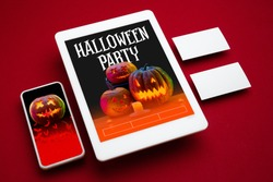 Scary pumpkin on device screen and red background. Jack-o-Lanterns with candles. Halloween, black friday, cyber monday, sales, party, autumn concept. Tablet and money card. Invite cards, promotion.