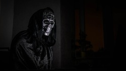 Scary reaper looks into laptop monitor, halloween character. Human skull.