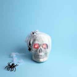 Scary skull mummy with glowing eyes and spider on blue background. Minimal Halloween concept.