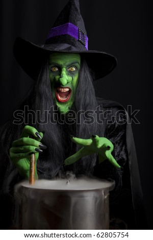 Scary witch stirring her cauldron. Low key lighting.