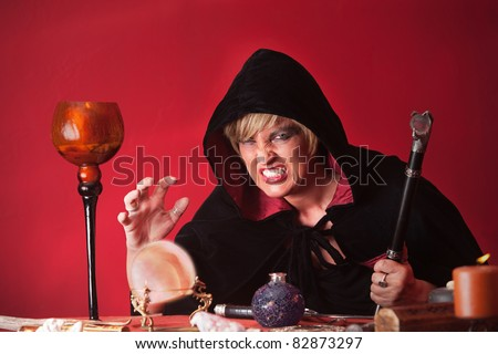 Scary witch with sceptre and crystal ball over red background