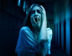 Scary woman screaming in a dark hallway.
